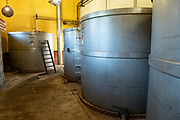 Giant fermentation tanks where blue agave mash is fermenting at the Casa Siete Leguas, El Centenario tequila distillery in Atotonilco de Alto, Jalisco, Mexico. After being crushed by a stone mill the agave fibers are mixed with spring water and fermented before being distilled into tequila. The Seven Leagues tequila distillery is one of the oldest family owned distilleries and produces handcrafted tequila using traditional methods.