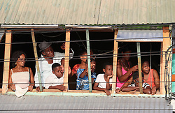 People await the arrival of Prince Harry from a first floor window, as he will tour a St Lucian street festival in Soufriere on the island of St Lucia during the second leg of his Caribbean tour.