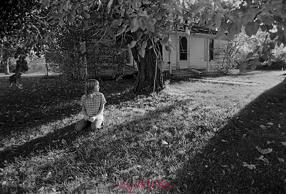 A young girl with the late afternoon sun in her face, sits in the front yard of her home in Quick City, Missouri, 1975.<br /> <br /> I photographed this scene on my return to Denver from the Missouri Photo Workshop held in Nevada, MO in 1975.
