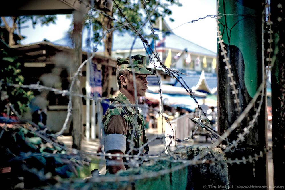 A Thai border guard, seen through barbed wire, watches the arrival station in Thailand near the Cambodian town of Koh Kong. Thai authorities at the station said if undocumented Cambodian migrants are discovered in Thailand they are sent to the Cambodian embassy in Bangkok where they are issued temporary passports. Cambodian officials on the other side of the border acknowledged truckloads of deportees are dropped at the border with regularity. They stated Thai authorities do not notify Cambodian Immigration officials when this occurs.