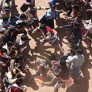Rival village groups fight in the streets of Macha during the Tinku Festival. Macha, Bolivia, 4th May 2010, Photo Tim Clayton ..Each May, up to 3000 thousands indigenous Bolivian indians descend on the isolated mountainous village of Macha 75 miles north of Potosi in the Bolivian Andes. The 600 year old pre-hispanic Bolivia Festival of Tinku sees villagers from all over the region march into town to be pitted against each other in a toe to toe fist to fist combat.. They dance and sing in traditional costume and drink 96% proof alcohol along with chicha, a fermented beverage made from corn. Townspeople and sometimes the police oversee proceedings who often use tear gas to try and control the villages, whipped into a fighting frenzy by the dancing and alcohol, but as the fiesta goes on things often escalate beyond their control, with pitched battles between rival villages break out,  The blood spilt is an offering to the earth goddess - Pachamama - to ensure a good harvest for the coming year. Over the years dozens have died, yet the rite continues.