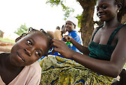 A woman arranges a younger girl's hair in the village of Dungu, Ghana on Friday June 8, 2007.