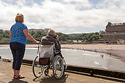 A man in a wheelchair, cared for by a middle aged woman,  takes photographs of the beach and bay at Scarborough, North Yorkshire.