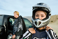 Motocross Racer Putting on Helmet