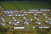 Unilever tea plantation workers' housing amidst the lush, rolling tea fields in the Kericho district, Kenya. (From the book What I Eat: Around the World in 80 Diets.)  The Kericho district in the Great Rift Valley has rich volcanic soil, cool air, and a moist tropical climate that's perfect for growing tea. With its popular tea brand Lipton, Unilever has helped make Kenya the number one exporter of black tea in the world. Since the evergreen tea bushes are picked every 14 to 17 days year-round, there is constant work for pickers. They're paid by the kilo of tea leaves and a field foreman reported that they can earn between $3 and $9 (USD) per day. To compete with Unilever and James Finlay, another huge corporate tea producer in Kenya, the Kenya Tea Development Agency represents half a million small-scale tea growers throughout Kenya.