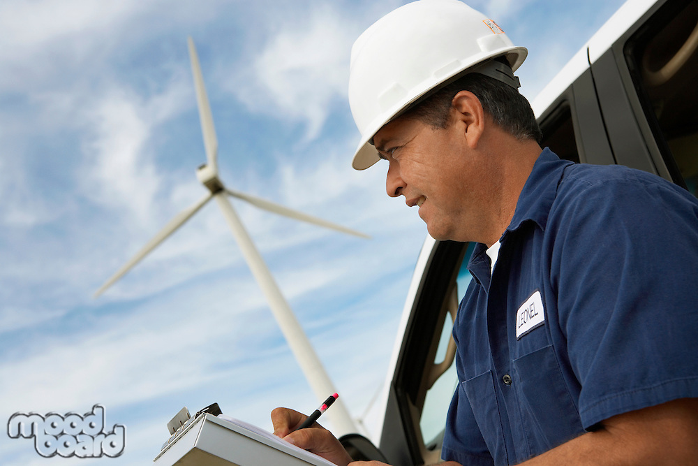 Engineer writing on clipboard by car at wind farm