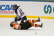 Robert Morris forward Greg Gibson takes down RIT defenseman Michael Holland during the Atlantic Hockey final at the Blue Cross Arena in Rochester on Saturday, March 19, 2016.
