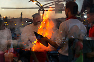 Busy evening scene of Moroccan men cooking barbecue dinner on an open fire at the famous Djemaa el Fna square, November 6, 2017, Marrakech, Morocco. Double exposure image. Editorial use only.
