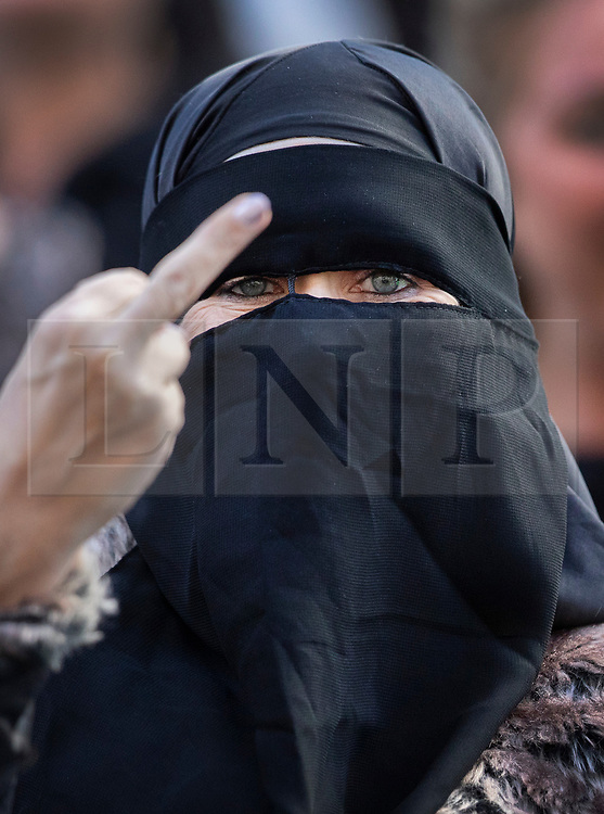 © Licensed to London News Pictures . 27/09/2018. London, UK. A woman wearing a full face veil gestures to photographers as she waits to catch sight of former EDL leader Tommy Robinson at the Old Bailey, where his retrial for Contempt of Court was adjourned - following his actions outside Leeds Crown Court in May 2018 . Robinson was already serving a suspended sentence for the same offence when convicted in May and served time in jail as a consequence , but the newer conviction was quashed by the Court of Appeal and a retrial ordered . Photo credit: Peter Macdiarmid/LNP