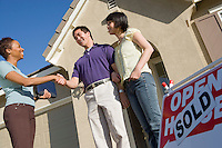 Couple shaking hands with estate agent outside their new home