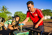 29 JUNE 2013 - BATTAMBANG, CAMBODIA:  A Bamboo Train driver buys gas from a girl in O Sra Lav, a small village southeast of Battambang. The bamboo train, called a norry (nori) in Khmer is a 3m-long wood frame, covered lengthwise with slats made of ultra-light bamboo, that rests on two barbell-like bogies, the aft one connected by fan belts to a 6HP gasoline engine. The train runs on tracks originally laid by the French when Cambodia was a French colony. Years of war and neglect have made the tracks unsafe for regular trains.  Cambodians put 10 or 15 people on each one or up to three tonnes of rice and supplies. They cruise at about 15km/h. The Bamboo Train is very popular with tourists and now most of the trains around Battambang will only take tourists, who will pay a lot more than Cambodians can, to ride the train.       PHOTO BY JACK KURTZ