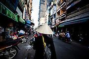 A Vietnamese woman wearing a conical hat walks along a street in Ho Chi Minh City, Vietnam, Southeast Asia
