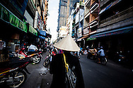 A Vietnamese woman wearing a conical hat walks along a street in Ho Chi Minh City, Vietnam, Southeast Asia