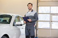 Portrait of confident male mechanic with clipboard standing by car in workshop