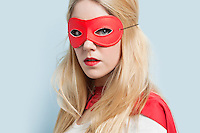 Portrait of a blond young woman wearing red eye mask against light blue background