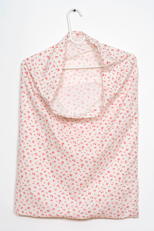 cushion cover hanging on a clothing hanger to dry