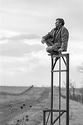 man sitting on top of a metal object on a ranch in New Mexico