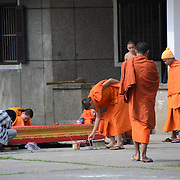 Buddhist monks and novices in their bright orange robes go about their daily chores at a wat in Luang Prabang, Laos.