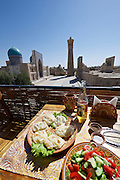Uzbekistan, Bukhara.<br /> Traditional Manty (steamed dumplings) in  a restaurant overlooking Kalon Minaret (r.) and Mir-i-Arab Medressa.