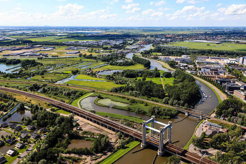 Nederland, Zuid-Holland, Gouda, 15-07-2012; spoorbrug over de Gouwe (viersporige hefbrug). Hoge Gouwebrug. Bedrijventerrein rond het riviertje, links de Zuidplaspolder, rechts Goudse Poort..Railway and lift bridge over the river Gouwe, business park in the back. .luchtfoto (toeslag), aerial photo (additional fee required).foto/photo Siebe Swart