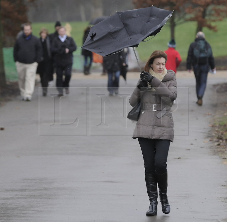 © Licensed to London News Pictures. 29/12/2012.Wet weather (today 29.12.12) in Greenwich Park,Greenwich, London..A woman holds on tight to her umbrella in Greenwich park. .today.Photo credit : Grant Falvey/LNP