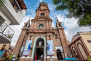 Looking up at the Puerto Vallarta church Our Lady of Guadalupe from close up with wide angle lens and full corners, lady in red standing in  doorway.