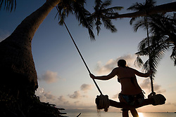 Young woman at sunset on a swing between palm trees in Thailand