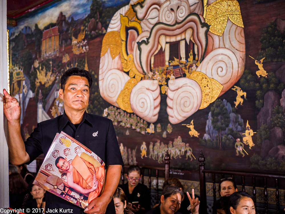 26 FEBRUARY 2017 - BANGKOK, THAILAND: A man holding portraits of Bhumibol Adulyadej, the King of Thailand, stands in line in front of a mural in Wat Phra Kaew. He was in line to pay respects to the king. Thousands of Thais continue to line up at the Grand Palace in Bangkok daily to pay respects to Bhumibol Adulyadej, the Late King of Thailand, who died on 13 October 2016. The government set a year long mourning period for the revered King, who will be cremated in late 2017.        PHOTO BY JACK KURTZ