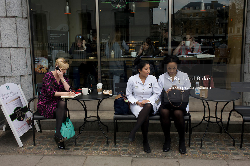 Shop assistants during a mid-day break sit together outside a Starbucks cafe in central London.