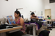 A Bolivian lady reading a CAMI leaflet in a sewing workshop. The leaflet hightlights some of the services offered by CAMI. These include; language courses, legal advice and skills workshops such as textiles.