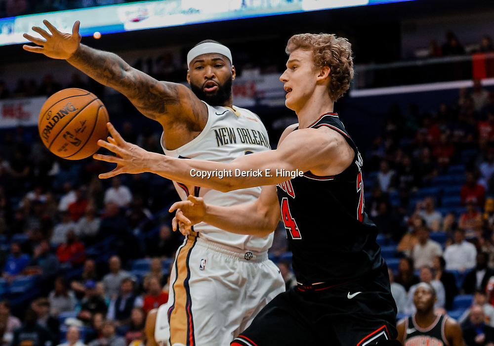 Jan 22, 2018; New Orleans, LA, USA; Chicago Bulls forward Lauri Markkanen (24) passes as New Orleans Pelicans center DeMarcus Cousins (0) defends during the first quarter at  the Smoothie King Center. Mandatory Credit: Derick E. Hingle-USA TODAY Sports