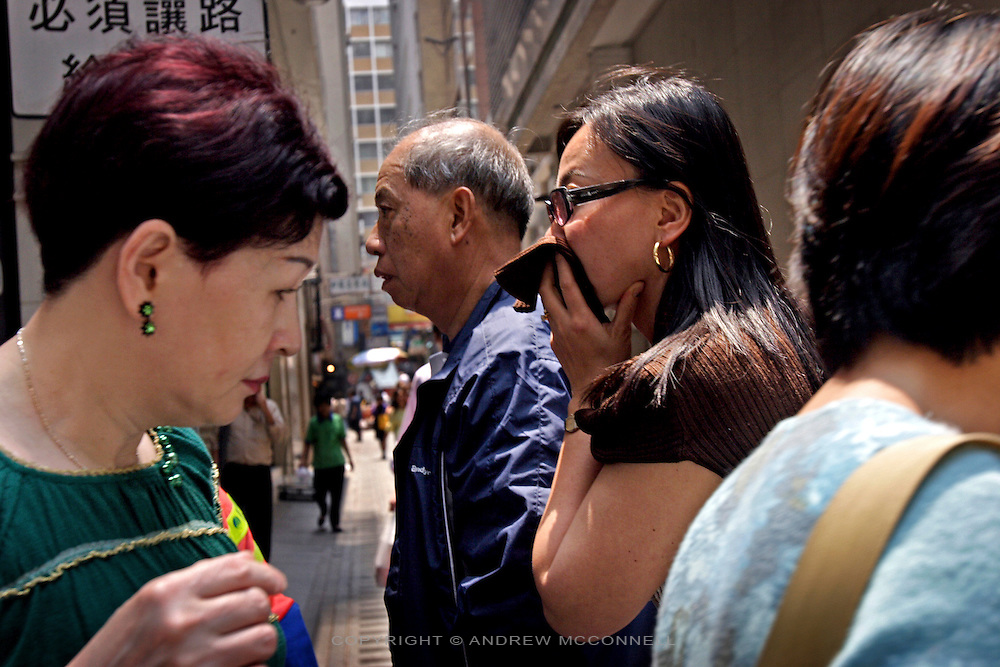 A woman covers her mouth to protect against the polluted air of Hong Kong.