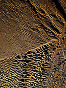 Closeup photo of abstract pattern created by  water in arroyo bed of Triassic period  mudstone.