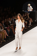 A white jumpsuit with cargo pockets in the legs, damask floral patterns in the fabric on the lower legs, and grid netting inset into the top.