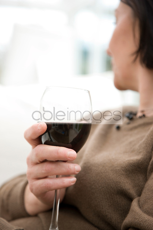 Close up of a woman holding a glass of red wine