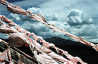 "China, Anye Machen, 2005. Prayer flags at a Qinghai ""mani ka,"" or prayer hill. Inscribed with verse, and tied to the highest places men can reach, prayers are released to heaven each time the wind blows.."