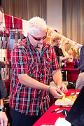 "Food Network Celebrity Chef Guy Fieri vists the Ergo Knives booth at the Grand Market during the Atlantic City Food & Wine Festival. Fieri promoted his ""Knuckle Sandwich"" line of culinary knives and accessories by signing knives, culinary accessories and t-shirts for a large group of fans."