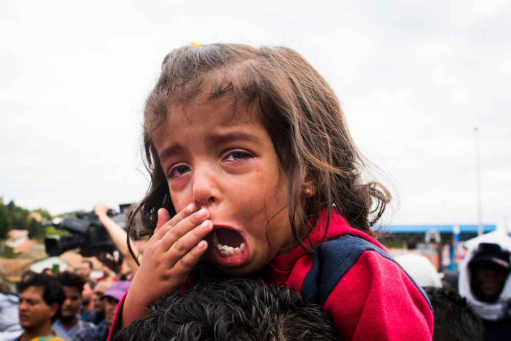 A young girl cries as Slovenian police prevent migrants from crossing the border on September 19, 2015 in Harmica, Croatia.