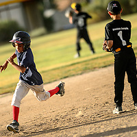 070114  Adron Gardner/Independent<br /> <br /> Red Sox Damian Dedrick (7), left, passes Pirate Jesse Baca (1) on his way to third base during the Roberto Clemente championship game at Father Dunston Park in Gallup Tuesday.