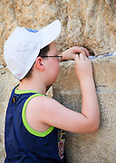 Israel, Jerusalem Old City, A young boy of six placing a note in the cracks of at the Wailing wall Model release available