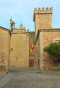 Historic buildings in medieval old town, Caceres, Extremadura, Spain - San Mateo church and flag on Torre de las Ciguenas