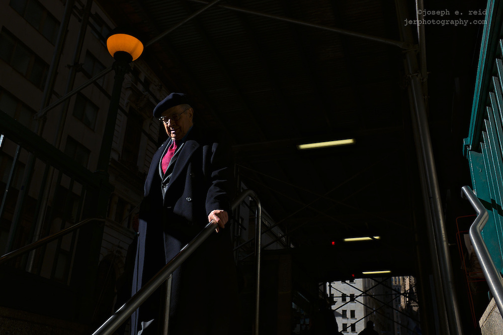Man in suit and cap entering subway station, New York, NY, US