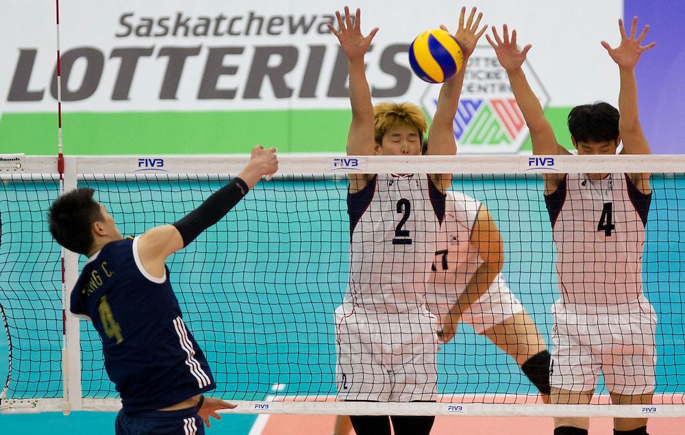 Sun-Soo Han (2) and Jin-Woo Park (4) of Korea block the spike of China's Chen Zhang (4) at a World League Volleyball match at the Sasktel Centre in Saskatoon, Saskatchewan Canada on June 26, 2016.