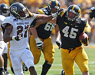 September 07 2013: Iowa Hawkeyes running back Mark Weisman (45) tries to hold off Missouri State Bears safety Brandon Cheaton (27) during the fourth quarter of the NCAA football game between the Missouri State Bears and the Iowa Hawkeyes at Kinnick Stadium in Iowa City, Iowa on September 7, 2013. Iowa defeated Missouri State 28-14.