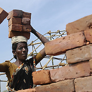 A woman carries bricks to construct a government-funded communal shelter in Perumalpettai, a fishing villlage in Tamil Nadu, India, on January 17, 2005, after people were left homeless when the Indian Ocean Tsunami struck on December 26, 2004. Generated by an earthquake on the ocean floor, the tsunami devastated the fishing industry along the southeastern coast of India.