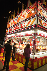 People wait in line at a hot dog on a stick stand at night, California Mid-State Fair, Paso Robles, California, United States of America