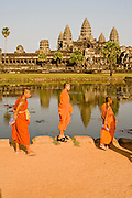 19 MARCH 2006 - SIEM REAP, SIEM REAP, CAMBODIA: Buddhist monks walk around the front of the main Angkor Wat complex, which is recflected in the moat that surrounds the complex near Siem Reap, Cambodia. Cambodian authorities estimate that more than one million tourists will visit Angkor Wat in 2006, making it the leading tourist attraction in Cambodia by a large margin. The complex is also one of the most important Buddhist religious centers in Cambodia.   Photo by Jack Kurtz / ZUMA Press
