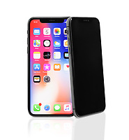 Two Apple iPhone X, large screen smartphones, product still life, one iPhone is leaning on another. The phones ares isolated on white studio background.