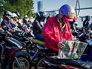 22 JANUARY 2019 - PHRA PRADAENG, SAMUT PRAKAN, THAILAND:  A man reads his morning newspaper on a motorcycle and vehicle ferry that crosses the Chao Phraya River in Phra Pradaeng, in the suburbs south of Bangkok. The use of vehicle ferries across the river has gone down as the government has built bridges to connect communities on both sides of the river. The Phra Pradaeng ferries are the busiest vehicle ferries in the Bangkok metropolitan area. Since the BTS Skytrain now comes close to the ferry, the number of commuters going into Bangkok that use the ferry has increased.     PHOTO BY JACK KURTZ