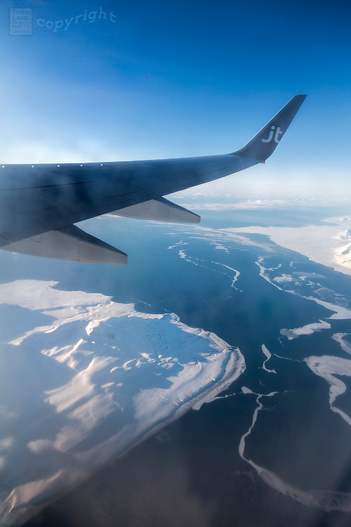 Airplane wing over frozen landscape